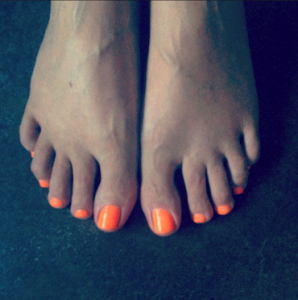 feet with orange nail polish